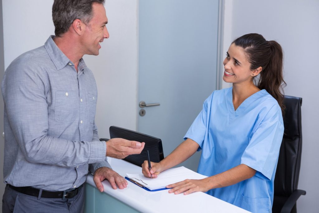 Smiling doctor and patient talking at desk